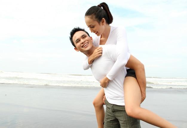 Portret szczęśliwa potomstwo para ma zabawę na plaży