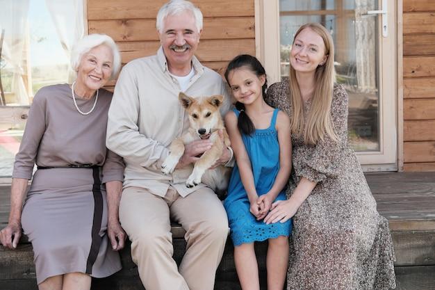 Portret szczęśliwa rodzina i ich pies siedzi na werandzie na zewnątrz i uśmiecha się