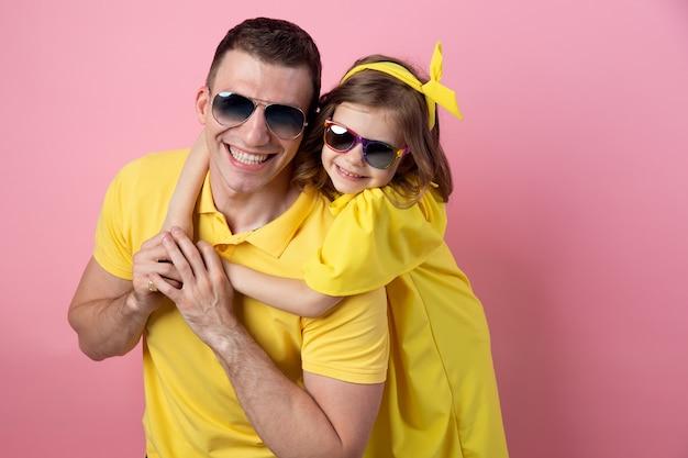 Portret szczęśliwa rodzina w żółtej odzieży z okularami przeciwsłonecznymi