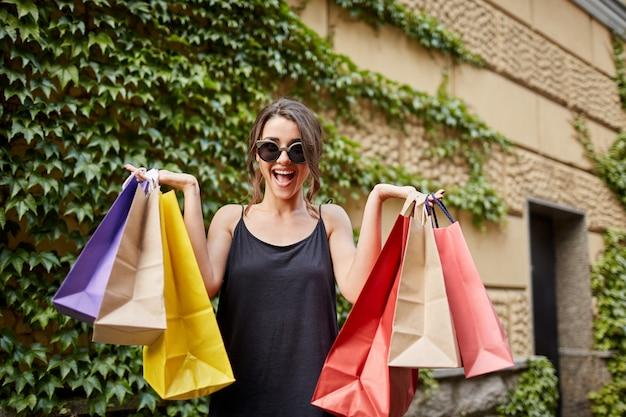 Portret szczęśliwa rozochocona młoda caucasian kobieta z ciemnym włosy w słońc szkłach i czarnym stroju patrzeje n kamerę z otwartym usta i szczęśliwym wyrażeniem, trzyma mnóstwo torba na zakupy z teraźniejszość.