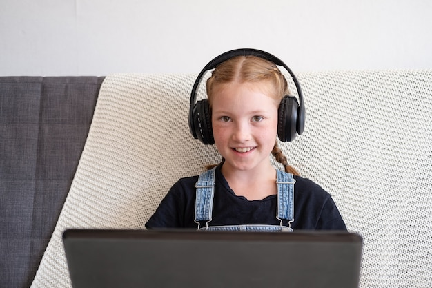 Portret szczęśliwa ruda dziewczyna w słuchawkach za pomocą laptopa podczas nauki w domu. powrót do szkoły