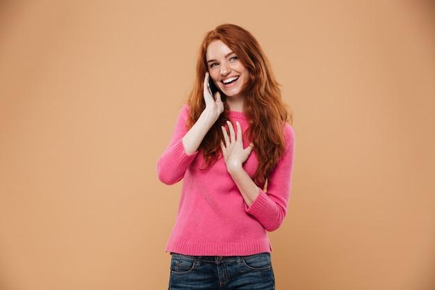 Portret szczęśliwa rudzielec dziewczyna opowiada na telefonie komórkowym