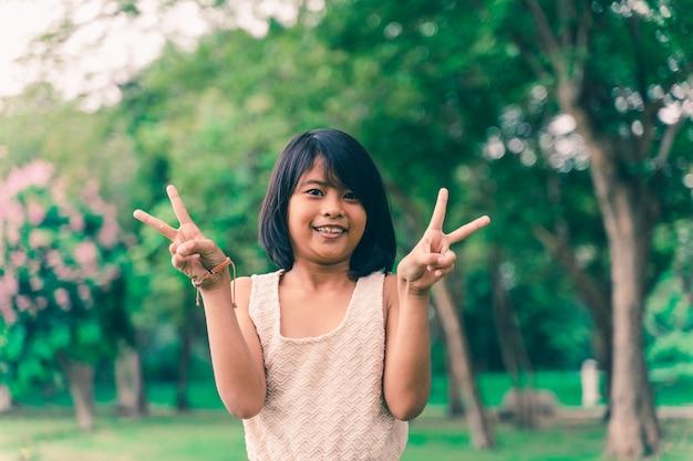 Portret szczęśliwa śliczna azjatykcia dziewczyna pokazuje różnorodnych gesty w parku