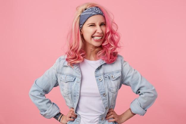 Portret szczęśliwa śliczna dziewczyna z różowymi włosami i wytatuowanymi rękami, patrząc na caera i mrugająca, uśmiechnięta i stojąca, ubrana w białą koszulkę i dżinsową kurtkę.