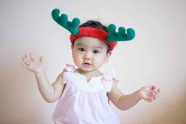 Portret szczęśliwa śliczna mała azjatycka dziewczyna, która właśnie miała zęby mleczne śmiejąc się. nosi kapelusz z poroża i patrzy w kamerę, na białym tle. koncepcja ekspresji dziecka
