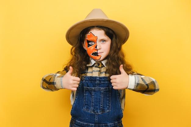 Portret szczęśliwa śliczna mała kaukaska dziewczynka dziecko z maską halloween makijaż, patrząc na kamery, pokazując kciuk do góry, pozowanie na białym tle nad żółtą ścianą tła studia. koncepcja świątecznych imprez