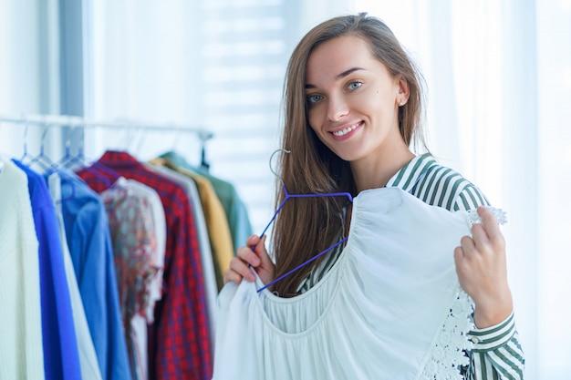 Portret szczęśliwa śliczna młoda brunetki kobieta próbuje nowożytną modną modną elegancką kobietę odziewa podczas zakupy i wybiera strój
