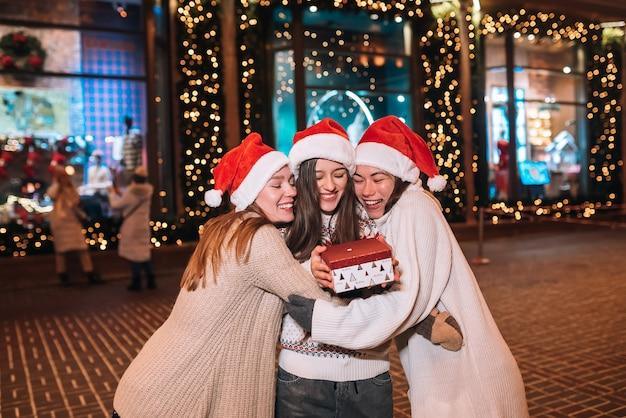 Portret szczęśliwa śliczna młoda grupa przyjaciół przytulających się i uśmiechających się podczas spaceru w wigilię bożego narodzenia na zewnątrz, w czapkach świętego mikołaja, wiele świateł na