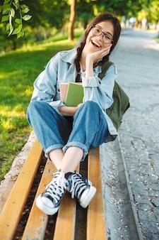 Portret szczęśliwa śliczna młoda studentka w okularach, siedząc na ławce na zewnątrz w parku przyrody, trzymając książki.