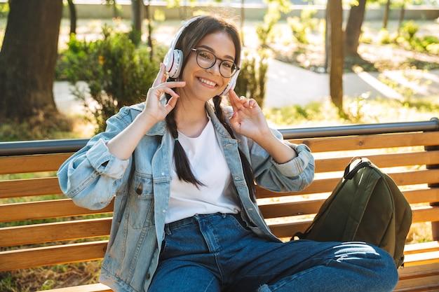 Portret szczęśliwa śliczna młoda studentka w okularach, siedząc na ławce na zewnątrz w parku, słuchając muzyki w słuchawkach.