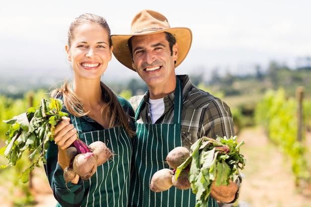 Portret szczęśliwa średniorolna para trzyma obfitolistnych warzywa