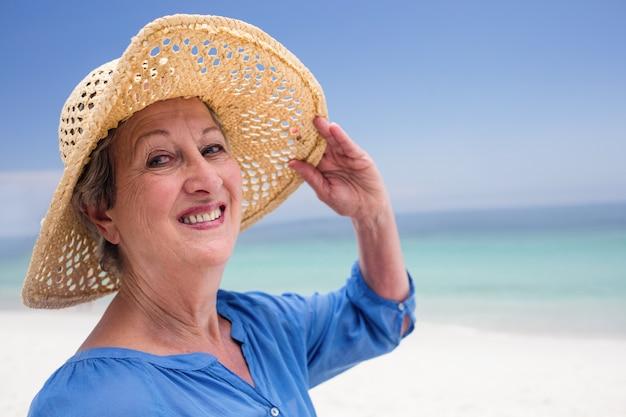 Portret szczęśliwa starsza kobieta w plażowym kapeluszu