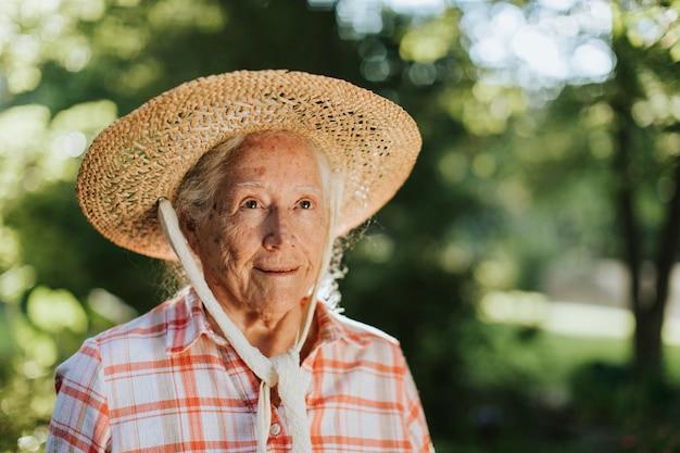 Portret szczęśliwa starsza kobieta z słomianym kapeluszem