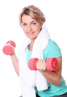 Portret szczęśliwa starzejąca się sportsmenka z dumbbells