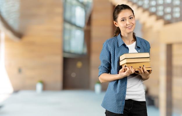 Portret szczęśliwa studencka dziewczyna lub kobieta z książkami w bibliotece
