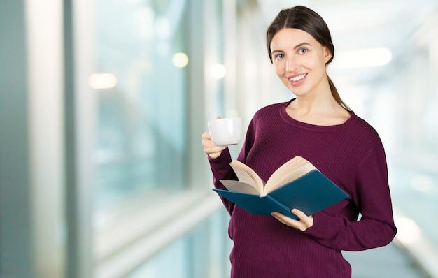 Portret szczęśliwa studencka kobieta z książkami w bibliotece