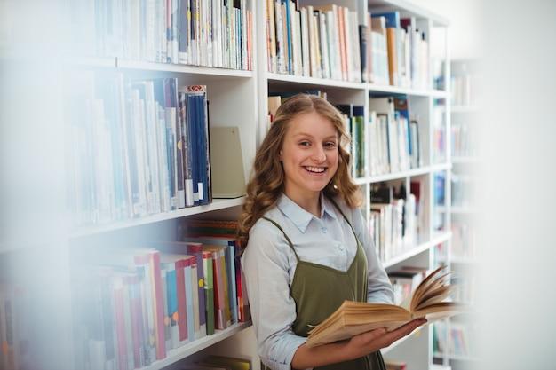 Portret szczęśliwa uczennica czytanie książki w bibliotece