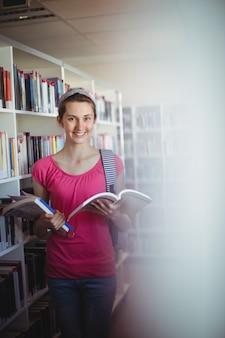 Portret szczęśliwa uczennica trzyma książkę w bibliotece