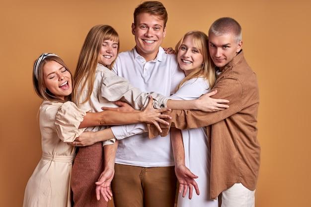 Portret szczęśliwa uśmiechnięta grupa młodzieży, pozowanie razem, nosząc modne płaszcze koszul