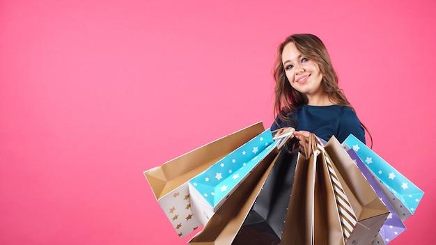 Portret szczęśliwa uśmiechnięta kobieta trzyma wiązkę pakunki po robić zakupy
