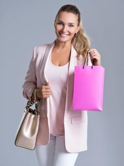 Portret szczęśliwa uśmiechnięta kobieta z różową torbą na zakupy
