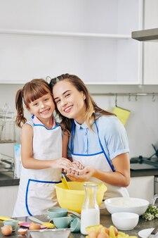 Portret szczęśliwa uśmiechnięta ładna kobieta i jej córeczka przytulanie i patrząc na kamery po zrobieniu ciasta