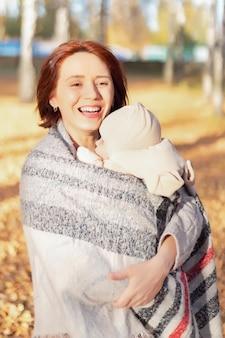 Portret szczęśliwa uśmiechnięta młoda kobieta z nowonarodzonym dzieckiem w ramionach w słoneczny dzień w parku miejskim