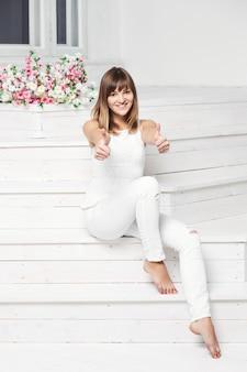 Portret szczęśliwa uśmiechnięta młoda piękna kobieta w białej codziennej odzieży, pokazując kciuk w górę gest