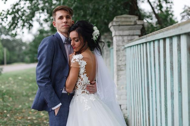 Portret szczęśliwa uśmiechnięta para narzeczonych na zewnątrz. właśnie małżeństwo na spacerze w zielonym parku wiosennym. emocjonalny nowożeńcy całują się i przytulają podczas spaceru weselnego. dzień ślubu.