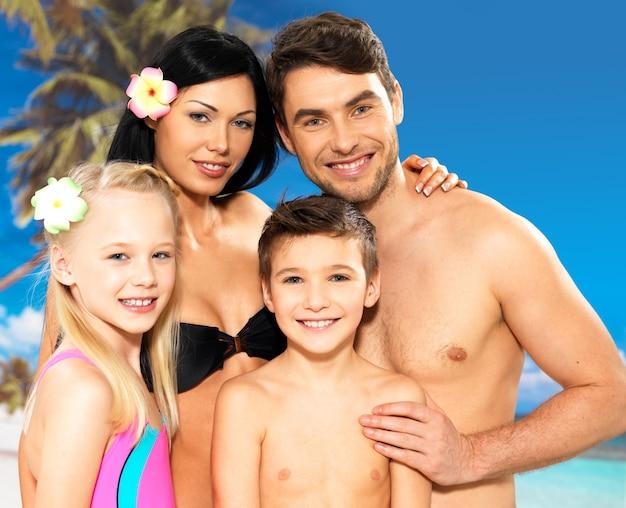 Portret szczęśliwa uśmiechnięta piękna rodzina z dwójką dzieci na tropikalnej plaży