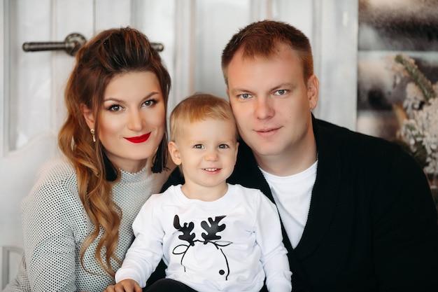 Portret szczęśliwa uśmiechnięta rodzina z uroczą blondynką patrząc na przód ze szczęścia