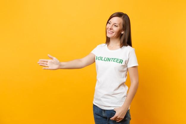 Portret szczęśliwa uśmiechnięta zadowolona kobieta w białej koszulce z napisem zielony tytuł wolontariusza na białym tle na żółtym tle. dobrowolna bezpłatna pomoc pomoc, koncepcja pracy łaski charytatywnej.