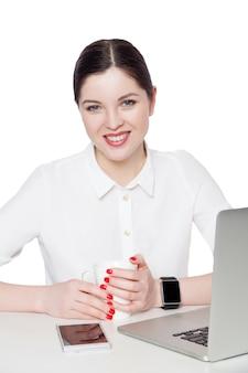 Portret szczęśliwa zadowolona atrakcyjna brunetka bizneswoman w białej koszuli siedzi, trzymając kubek napoju i patrząc na kamerę z toothy uśmiechem. kryty strzał studio, odizolowane w białym tle.