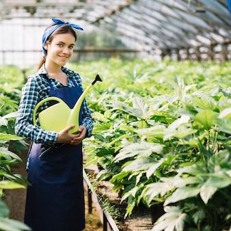 Portret szczęśliwa żeńska ogrodniczki mienia podlewania puszka w szklarni