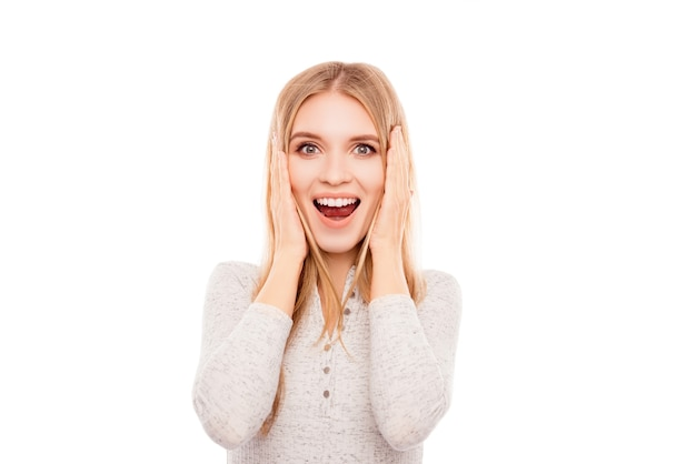Portret szczęśliwa zszokowana młoda kobieta z otwartymi ustami dotyka twarzy