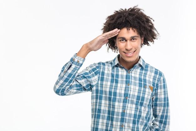 Portret szczęśliwego afro-amerykańskiego mężczyzny pozdrawiającego na białym tle na białej ścianie