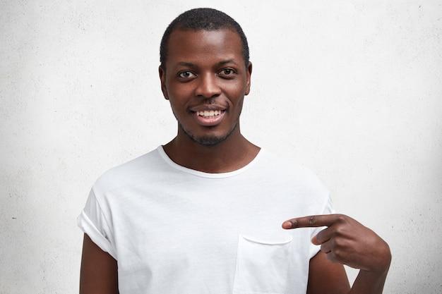 Portret szczęśliwego afroamerykanina o zadowolonym wyrazie twarzy, radośnie się uśmiecha, reklamuje nowy strój, zadowolony z zakupów