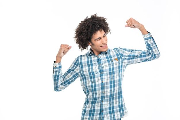 Portret szczęśliwego afroamerykańskiego mężczyzny pokazującego jego biceps na białym tle na białej ścianie