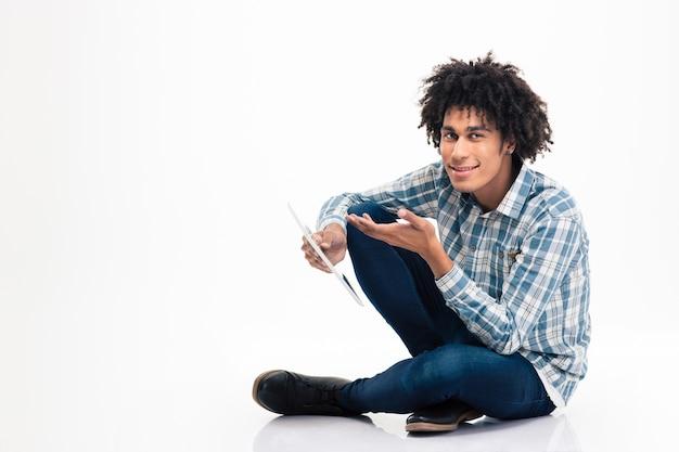 Portret szczęśliwego afroamerykańskiego mężczyzny siedzącego na podłodze z komputerem typu tablet na białym tle na białej ścianie