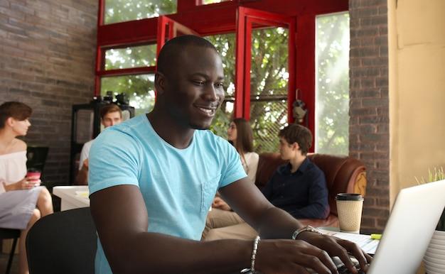 Portret szczęśliwego afroamerykańskiego przedsiębiorcy wyświetlającego komputer w biurze