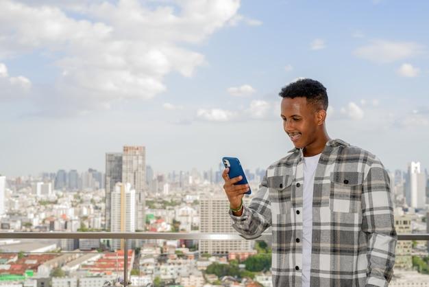 Portret szczęśliwego afrykańskiego czarnego mężczyzny na zewnątrz w mieście na dachu latem przy użyciu telefonu komórkowego podczas uśmiechania się poziomego ujęcia