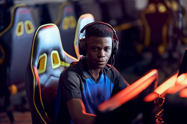 Portret szczęśliwego afrykańskiego faceta, profesjonalnego gracza w słuchawkach, patrzącego w kamerę i uśmiechającego się podczas udziału w turnieju esport, siedzącego w klubie gier lub kafejce internetowej