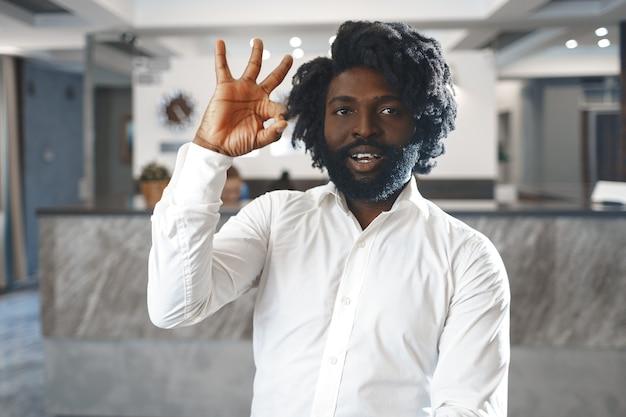 Portret szczęśliwego afrykańskiego managera hotelu lub gościa stojącego przed hotelową recepcją