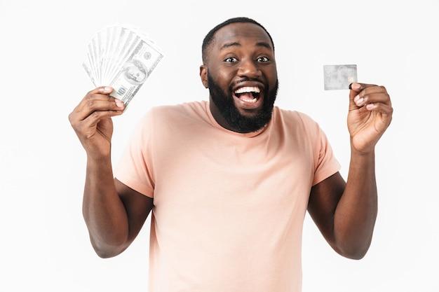 Portret szczęśliwego afrykańskiego mężczyzny noszącego koszulę stojącego na białym tle, pokazującego banknoty pieniędzy i kartę kredytową