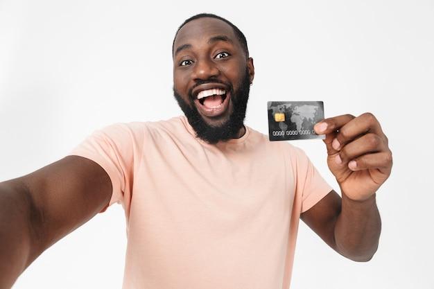 Portret szczęśliwego afrykańskiego mężczyzny w koszulce stojącego na białym tle nad białą ścianą, biorącego selfie, pokazującego kartę kredytową