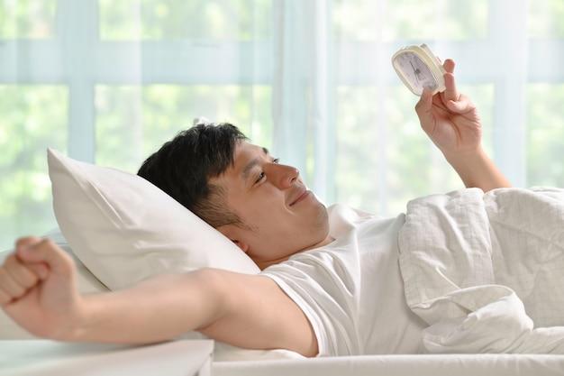 Portret szczęśliwego azjatyckiego mężczyzny budzącego się rano w łóżku