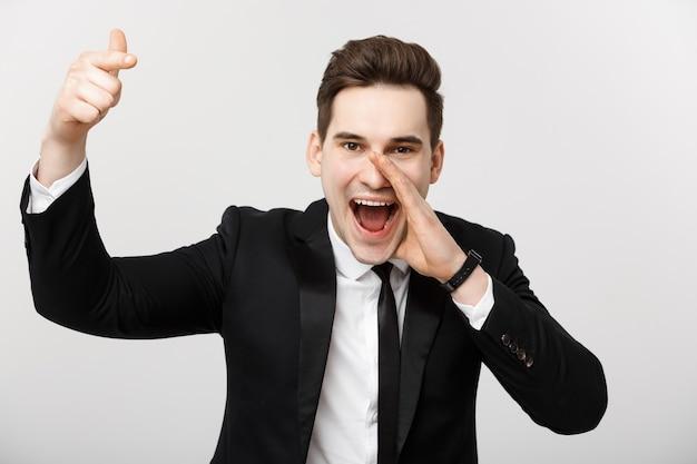 Portret szczęśliwego biznesmena w garniturze wskazującego palec na odosobnionym szarym tle