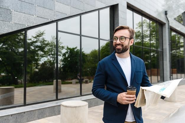 Portret szczęśliwego biznesmena w okularach, pijącego kawę z papierowego kubka i czytającego gazetę, stojąc na zewnątrz w pobliżu budynku