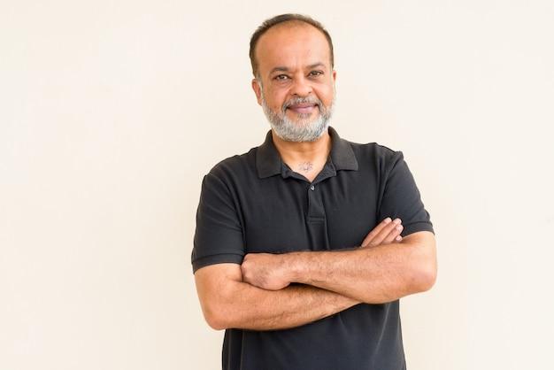 Portret szczęśliwego brodatego mężczyzny indyjskiego uśmiechającego się o zwykłą ścianę
