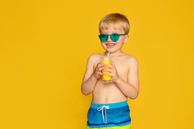 Portret szczęśliwego chłopca dziecka 6-7 lat w szortach kąpielowych z sokiem w dłoniach na żółtym tle, morze i lato